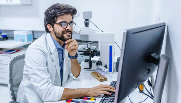 A doctor sitting at his computer and happy with his EHR software