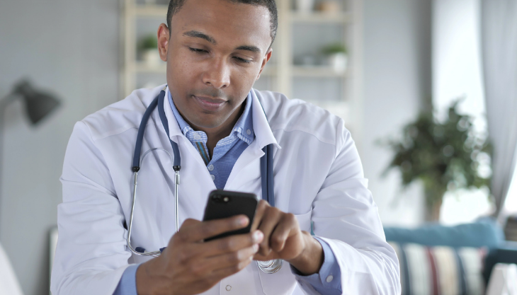A doctor using mobile EHR software on his smartphone