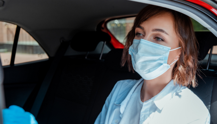 Woman with a mask sitting in the back of a non-medical transportation uber