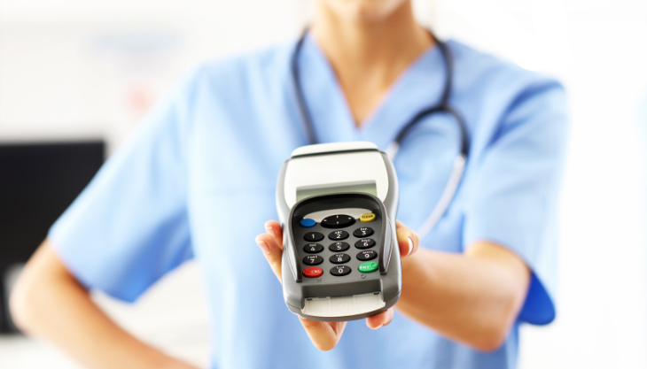 Doctor holding a credit card reader for easy payments