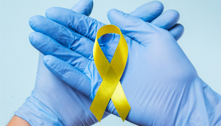Gloved hands holding a yellow ribbon for World Suicide Prevention Day