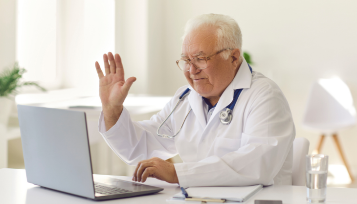 Doctor waving at a laptop screen during a telehealth video call.