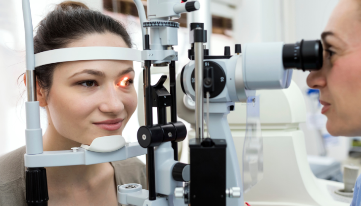A woman receiving an eye exam from a doctor using an ophthalmology EHR software